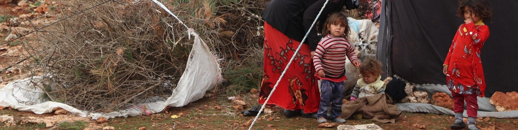 Tre bambini e una donna vicino alla tenda di un campo profughi.