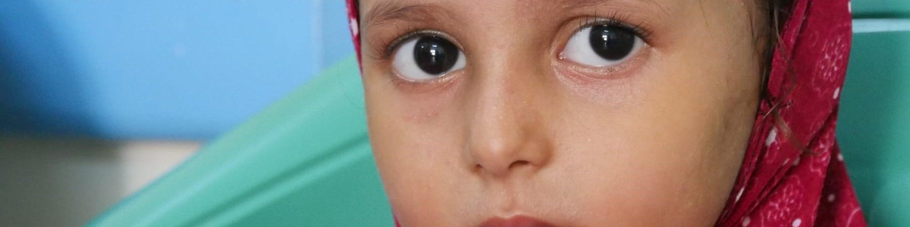 Primo piano bambina yemenita con velo rosso