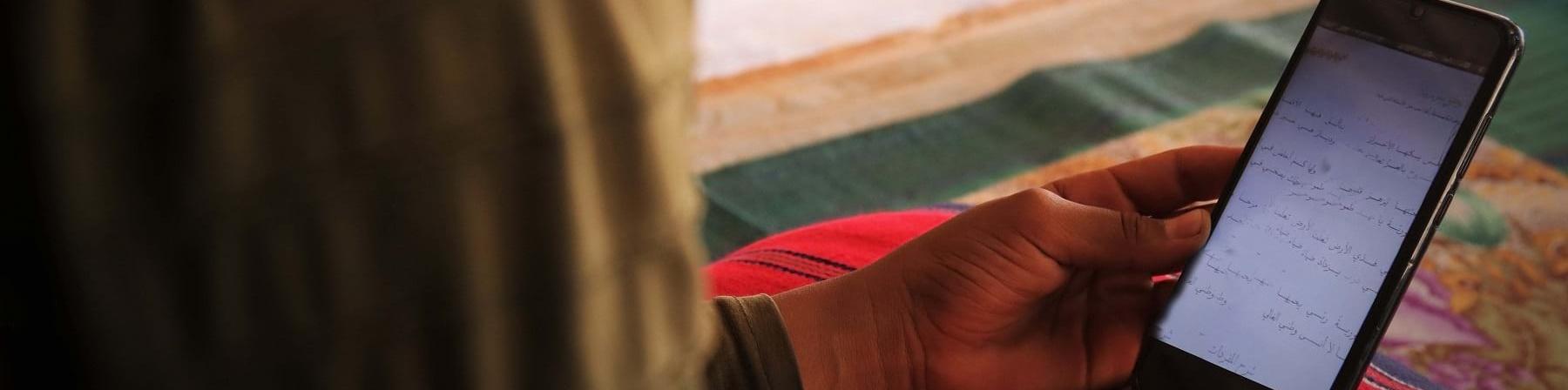 Profilo mezzo busto di un bambino che tiene in mano un cellulare e lo guarda