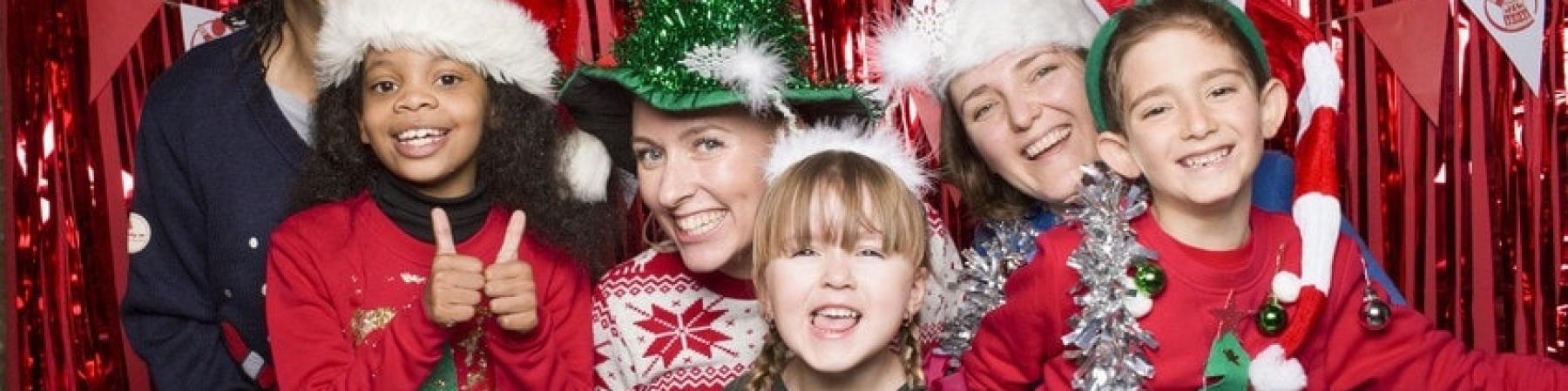 tre bambini e tre adulti vestiti con maglioni natalizi per il christmas jumper day