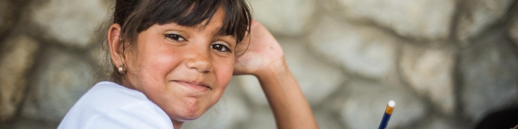 bambina di carnagione chiara-olivastra, con capelli castani legati con frangia, è seduta a un banco di scuola e guarda in camera mentre tiene una matita in mano.