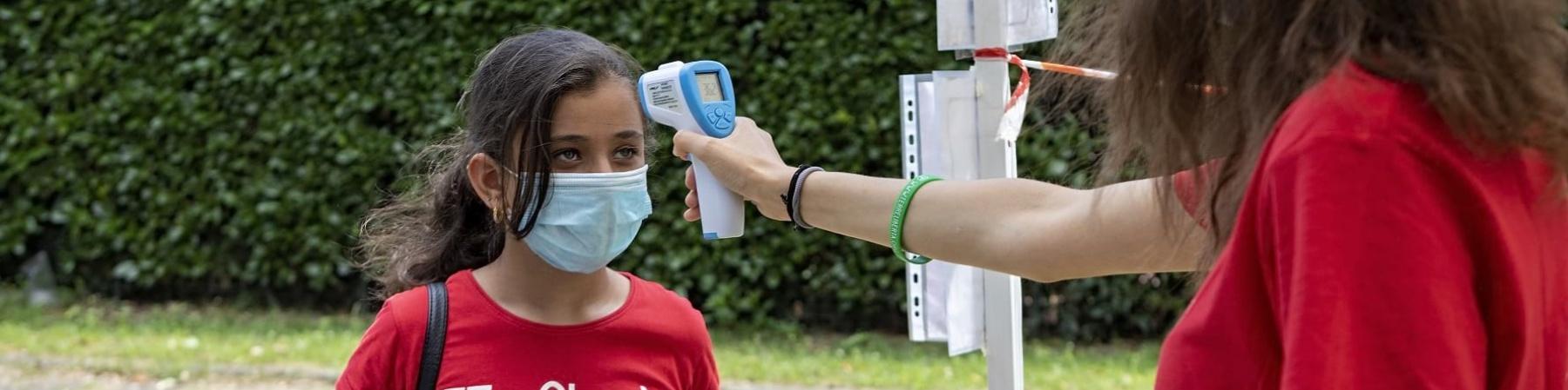 una operatrice misura la febbre con il termo scanner a una bambina con la mascherina chirurgica