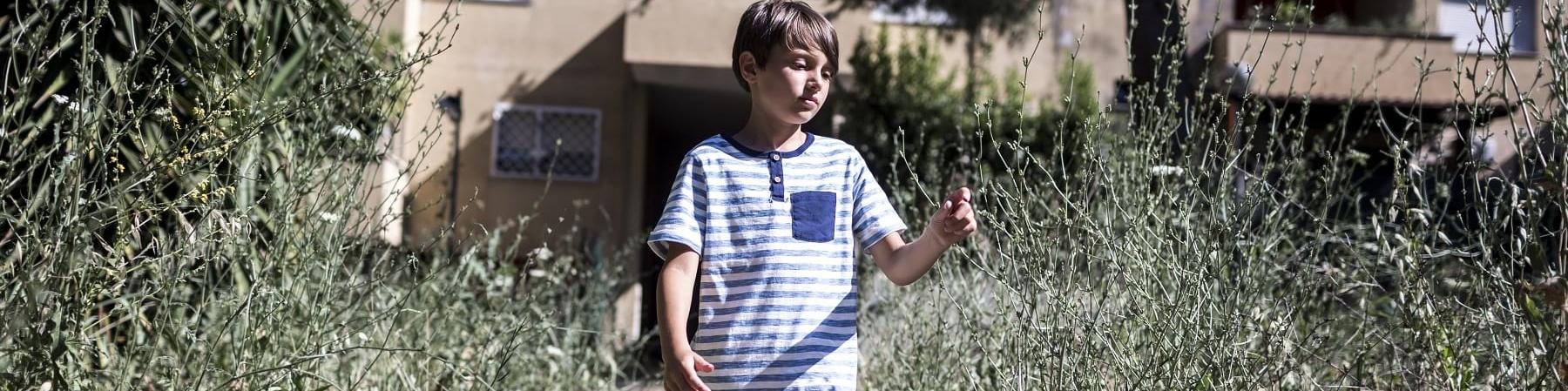 Un bambino con maglietta a righe e pantaloncini cammina in una viale sterrato con ai bordi erba alta