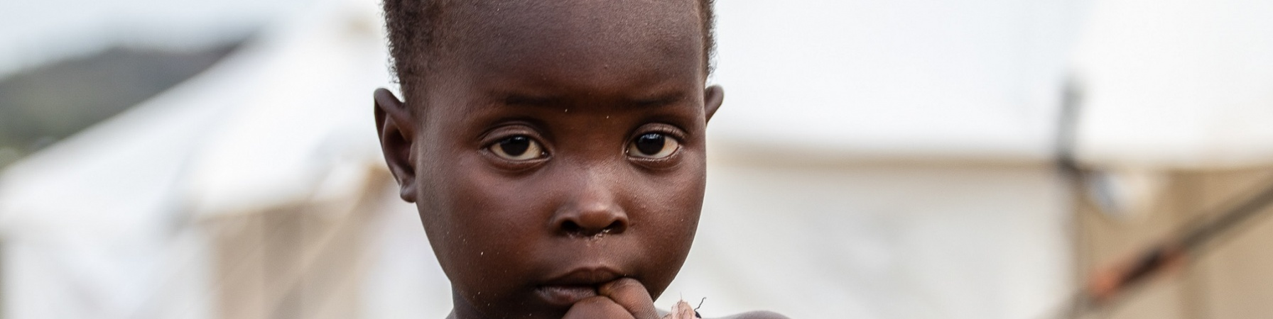 Bambina in primo piano con mano in bocca