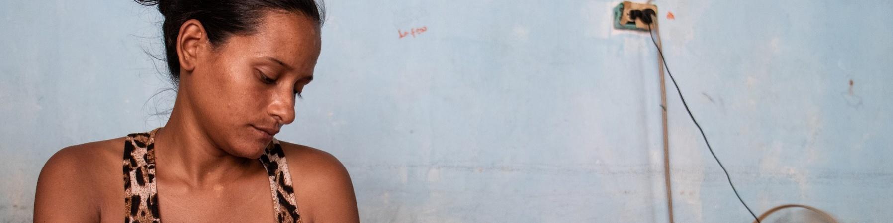 Donna venezuelana seduta su un letto tiene in braccio e guarda il figlio neonato.