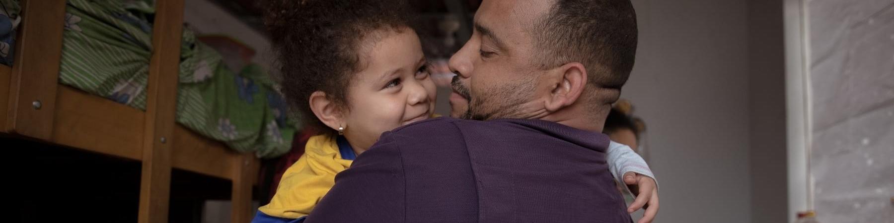 Un papà tiene in braccio e sorride a sua figlia