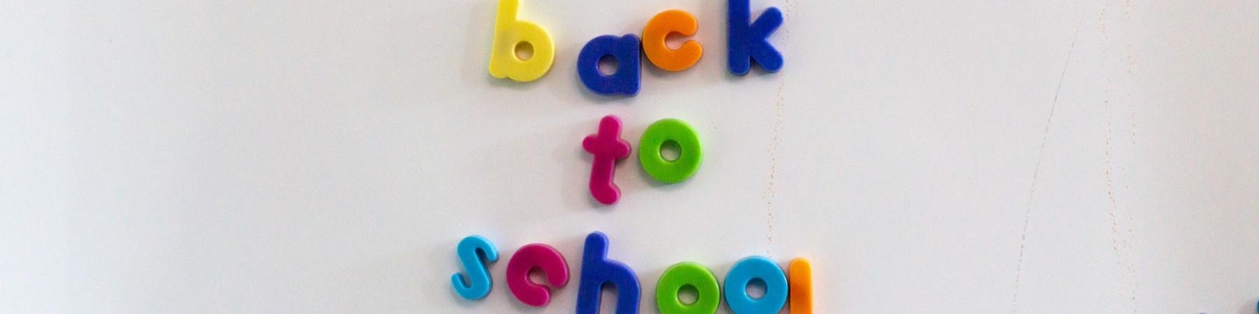 """lavagnetta magnetica con lettere colorate unite a formare la scritta """"Back to school"""""""
