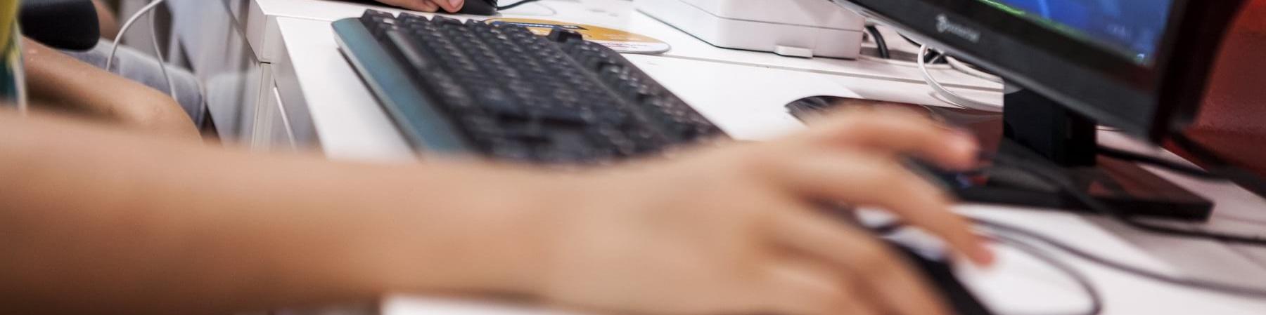 tavolo su cui sono posizionati vari computer con schermo, tastiera e mouse. Nell inquadratura alcune mani intente a lavorare con il mouse
