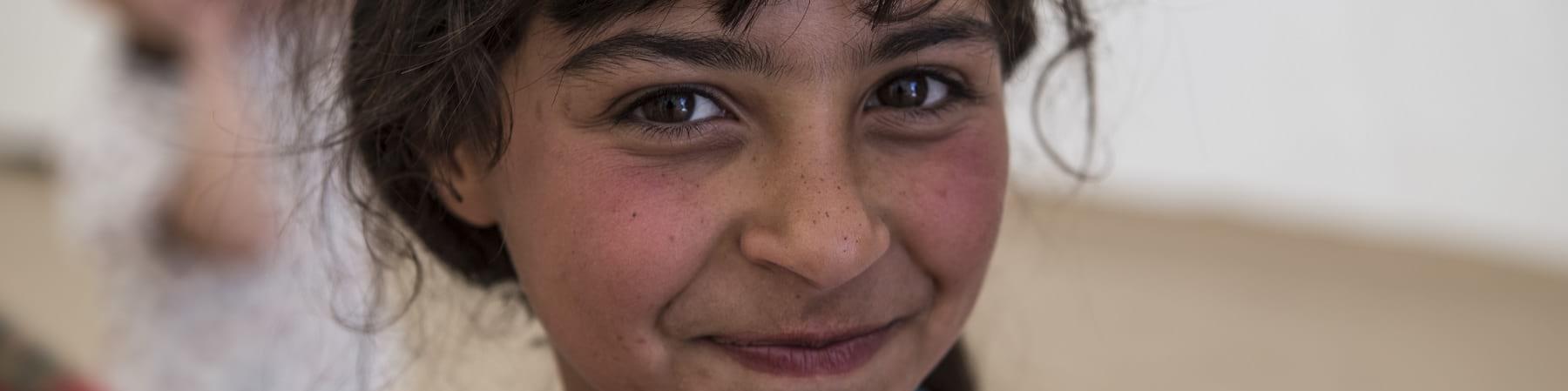 Primo pano di bambina bionda con capelli biondi legati e sguardo sorridente