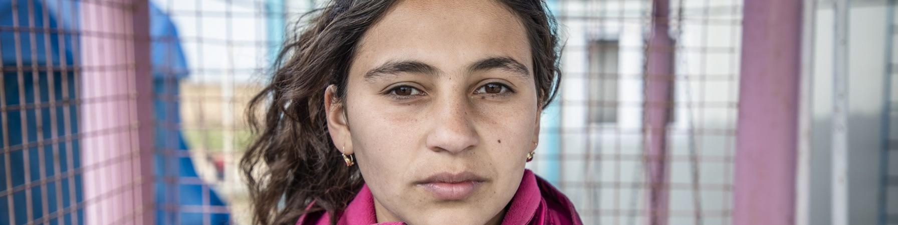Mezzo busto di una bambina siriana castana in campo per sfollati con giacca rosa