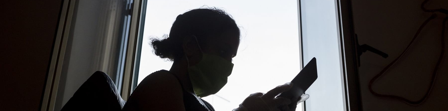 Sagoma nera in controluce di una bambina davanti a una finestra che tiene in mano un tablet e ne guarda lo schermo