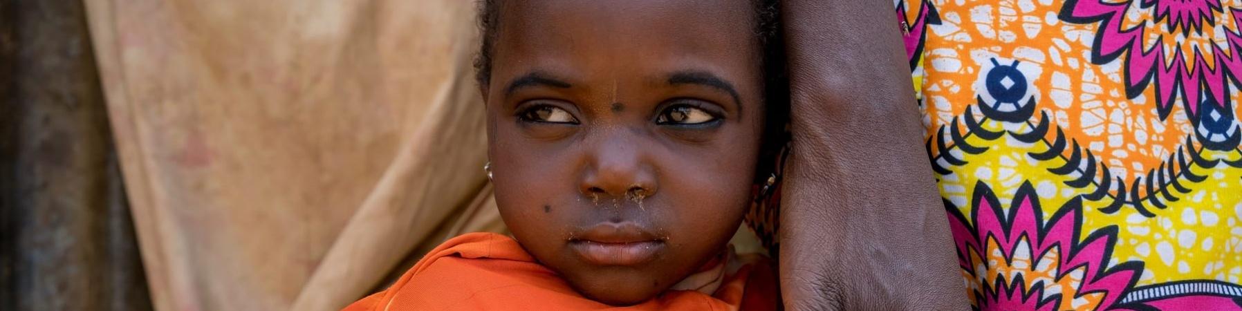 Primo piano di una bambina nigeriana con indosso una maglietta arancione che tiene per mano la mamma