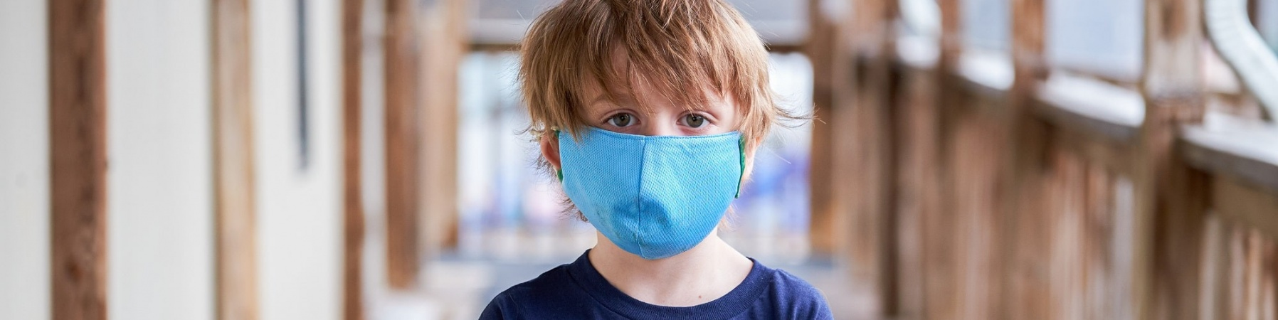 bambino con mascherina in piedi con le braccia conserte guarda in camera