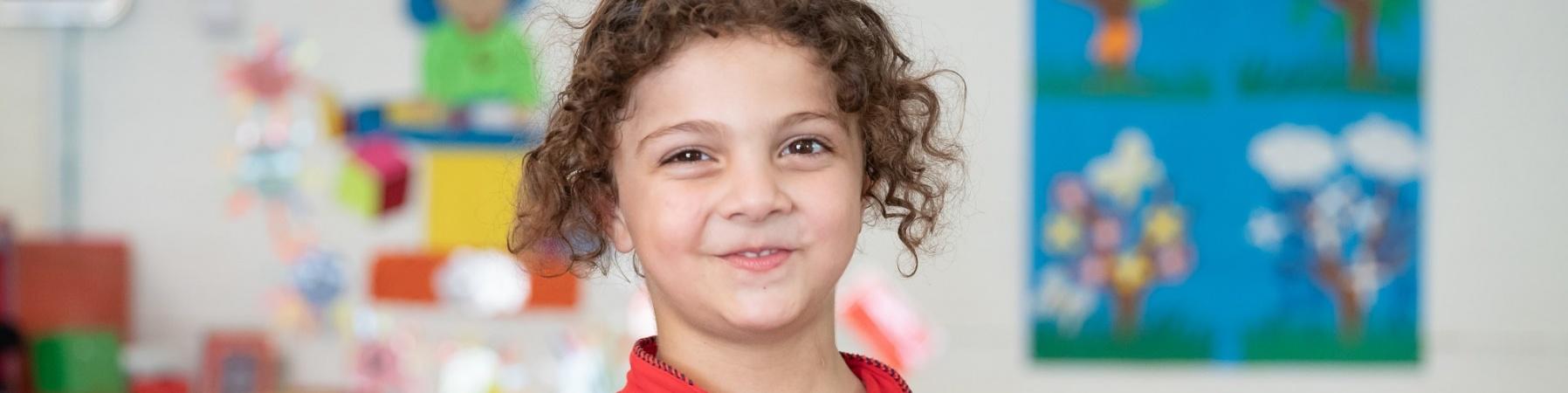 bambina sorridente con felpa rossa