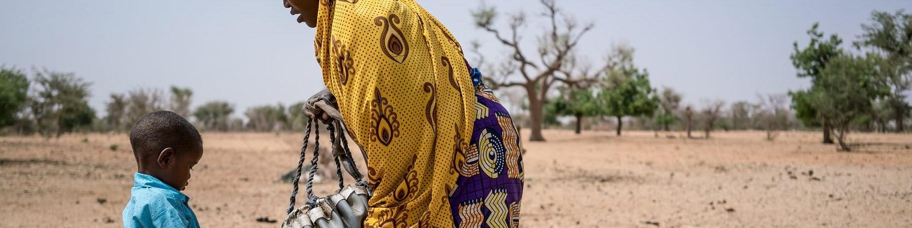 Campo lungo di madre e figlio nigeriani che si riforniscono di acqua in una terra brulla