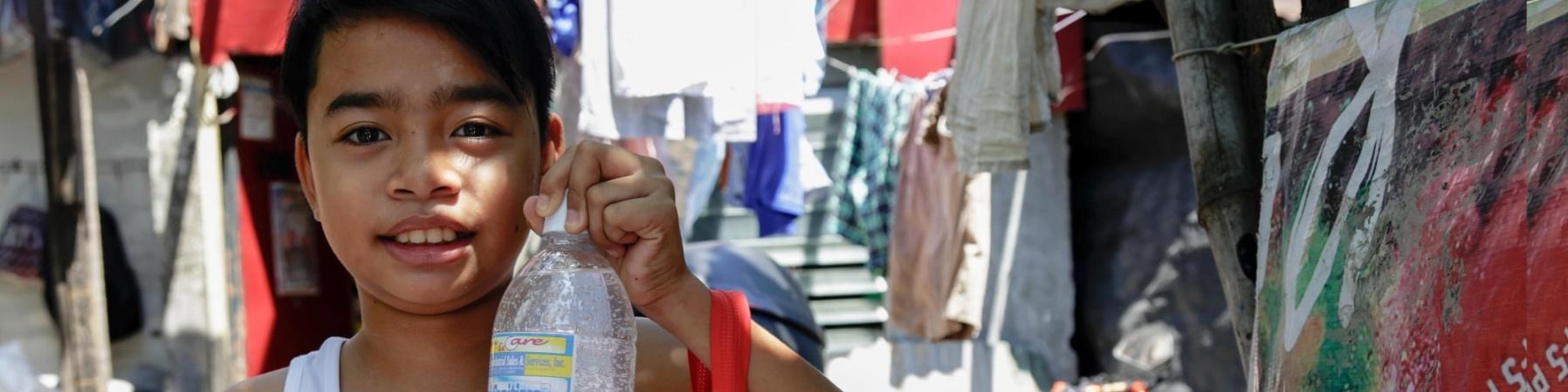 bambino asiatico tiene una bottiglia di acqua e un kit igienico sanitario in mano