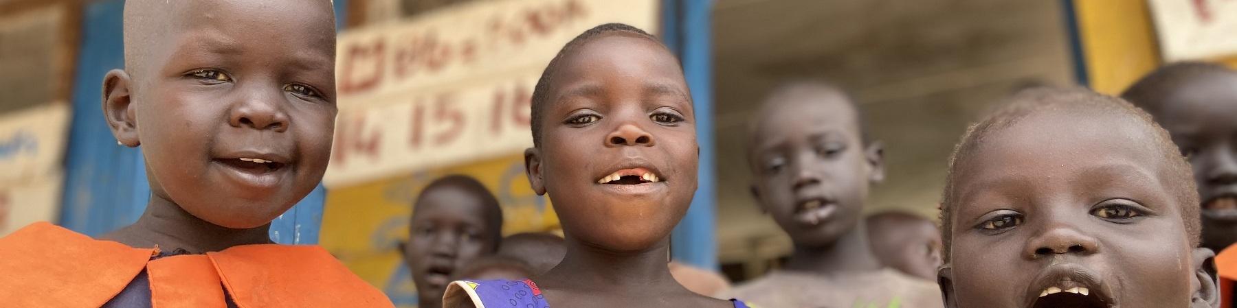 Tre bambini ugandesi in primo piano sorridono in camera. Sullo sfondo struttura in legno della scuola