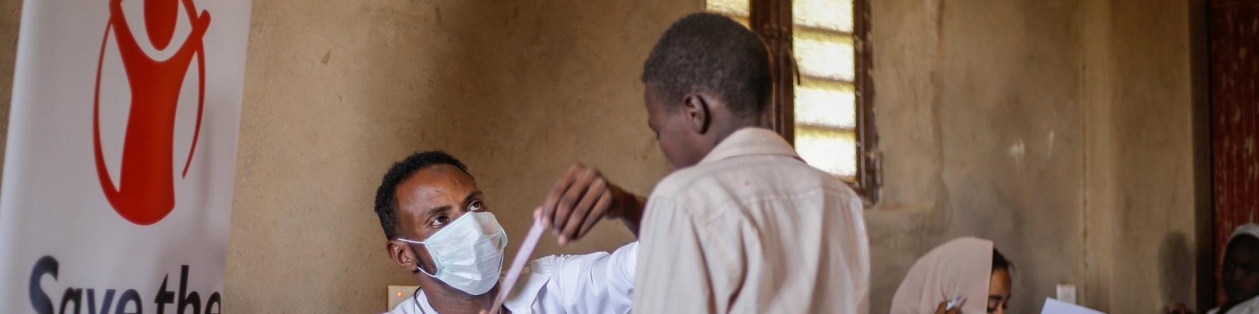 Sudan un operatore con mascherina visita un bambino in piedi di fronte a lui