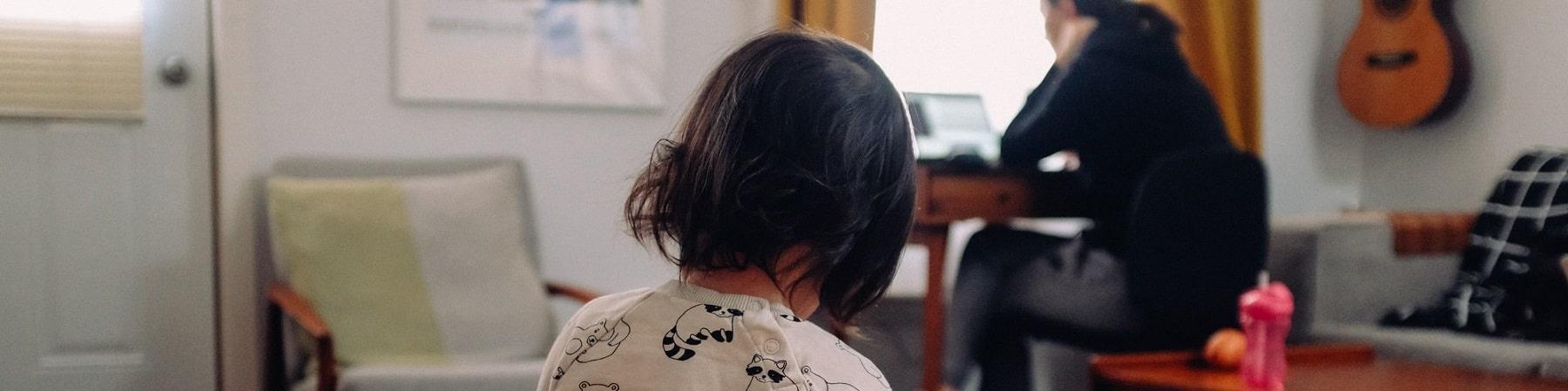 bimba in primo piano di spalle che gioca in casa e sullo sfondo la mamma che lavora al pc