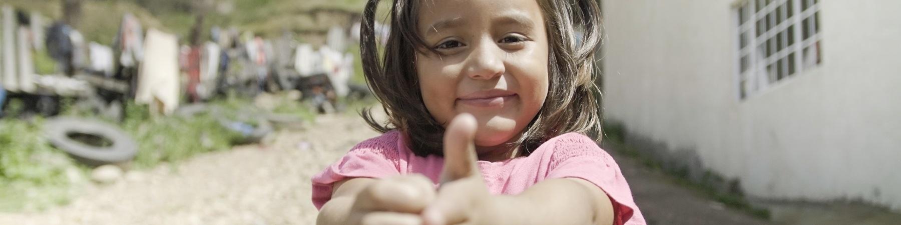 Una bambina messicana con codini e maglietta rosa mostra come ha imparato a lavarsi le mani.