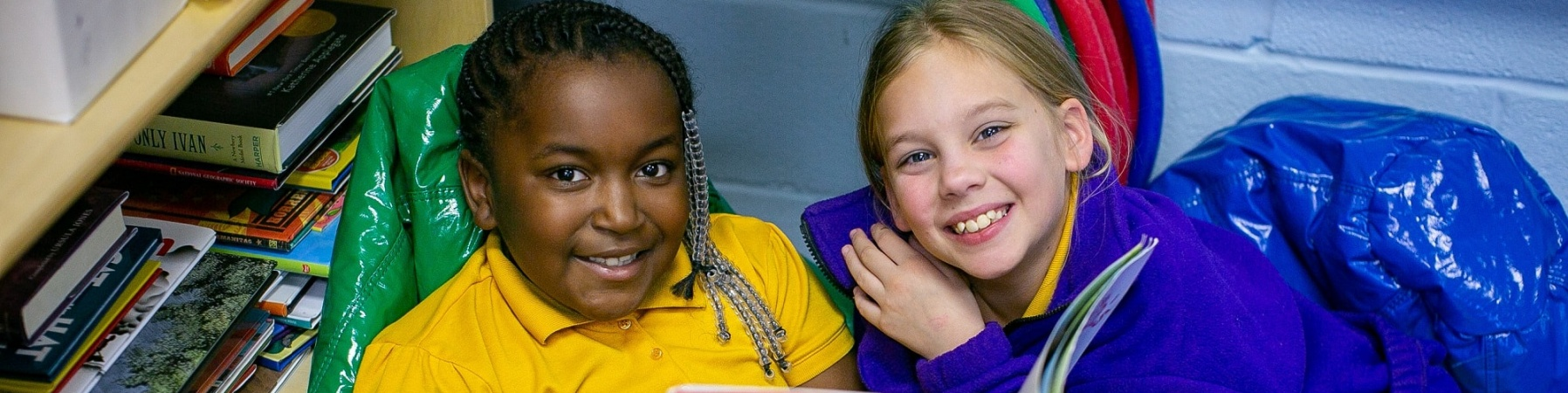 due bambine sedute su puff colorati leggono insieme