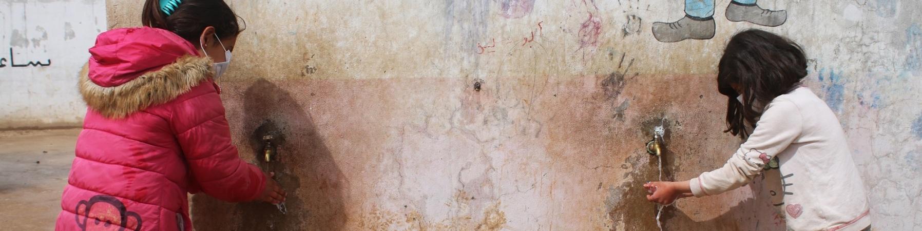 due bambine con mascherina in piedi davanti a un muro mentre si lavano le mani