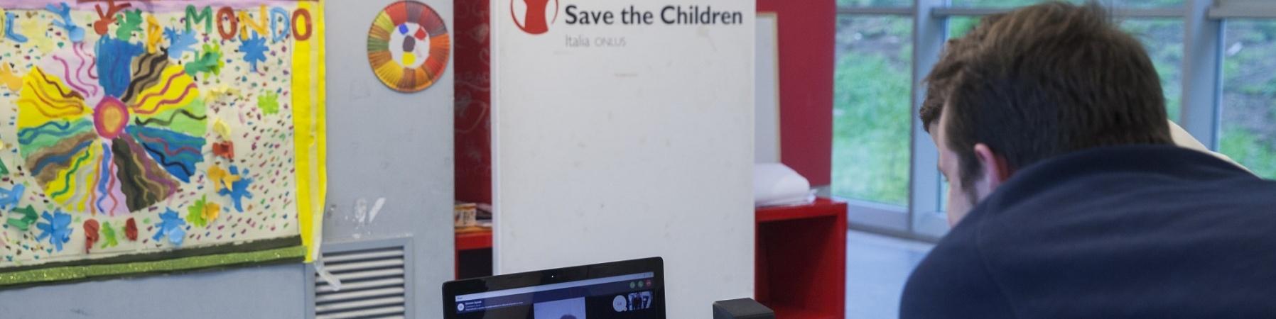 operatore di save the children italia davanti al pc in collegamento con un ragazzo