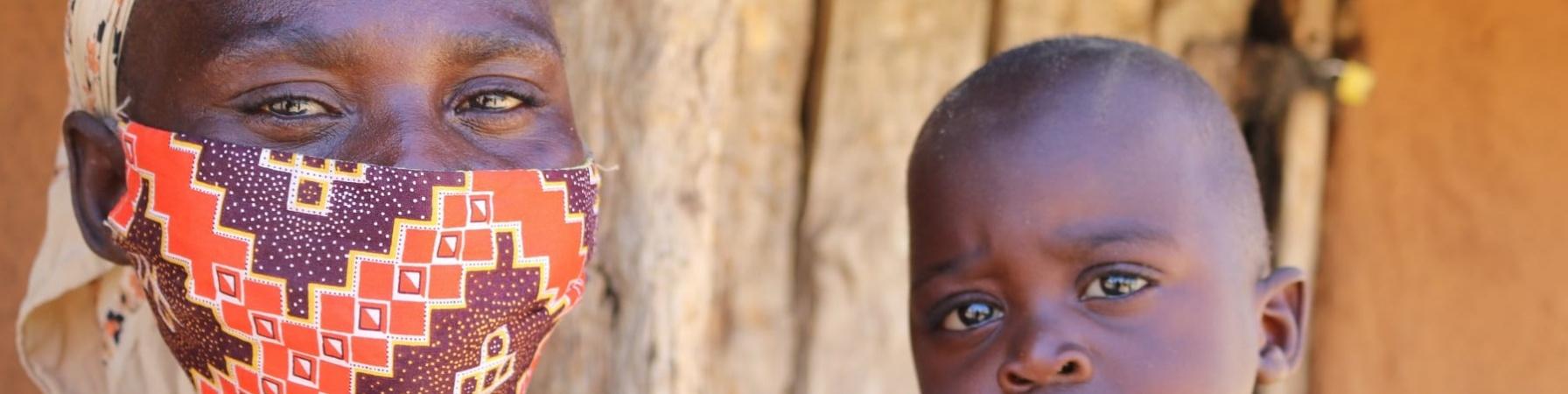 Mamma dello Zimbabwe con mascherina anti-covid tiene in braccio il suo bambino