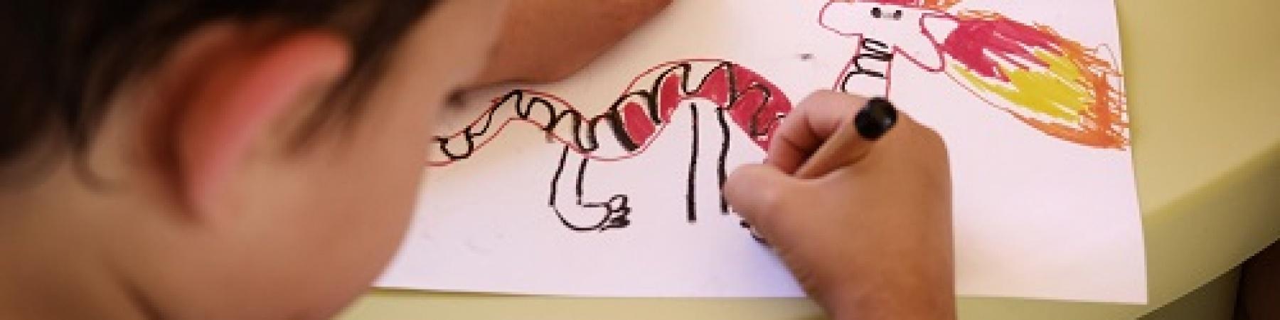 bambino di spalle che disegna un drago