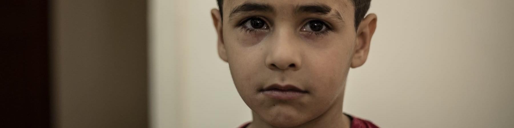 Primo piano ritratto di un bambino di circa sei anni libanese. Ha capelli corti, occhi e capelli bruni. Indossa una maglietta rossa