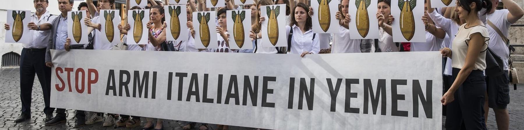 """Gruppo di persone davanti a Monte Citorio tengono uno striscione con la scritta """"Stop armi italiane in Yemen"""""""