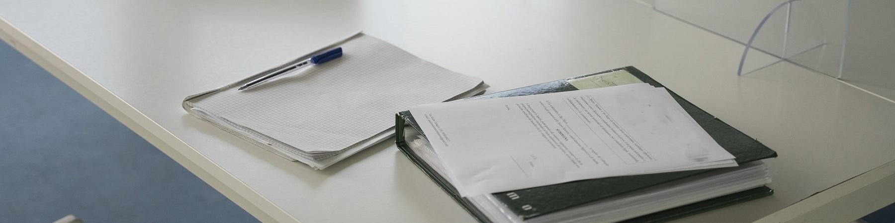 tavolino bianco con divisorio in plexiglass con sopra schedario, penna, un lap top e alcuni fogli
