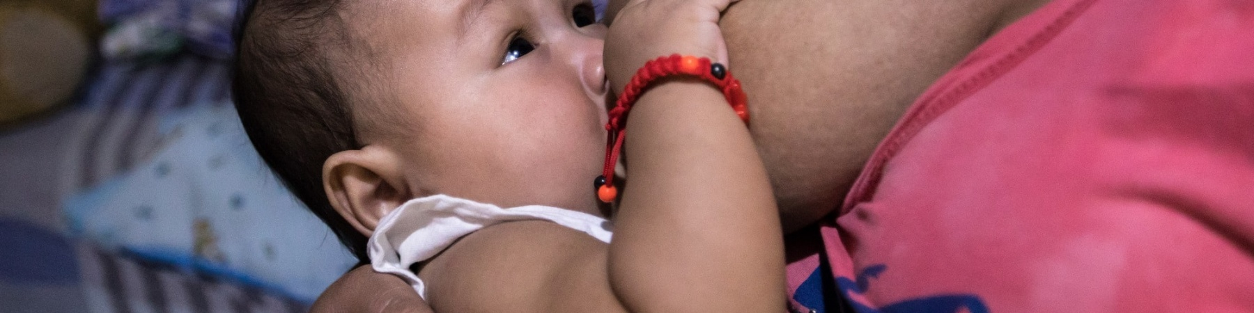 bambino allattato seno mamma con maglia rosa