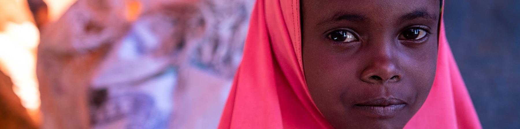 Primo piano di una bambina sola con un chador rosa fucsia
