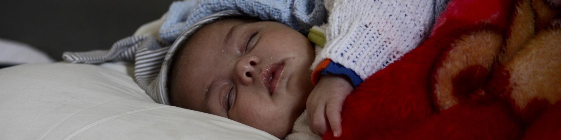 mezzo busto di bimbo che dorme in un lettino con sopra delle coperte