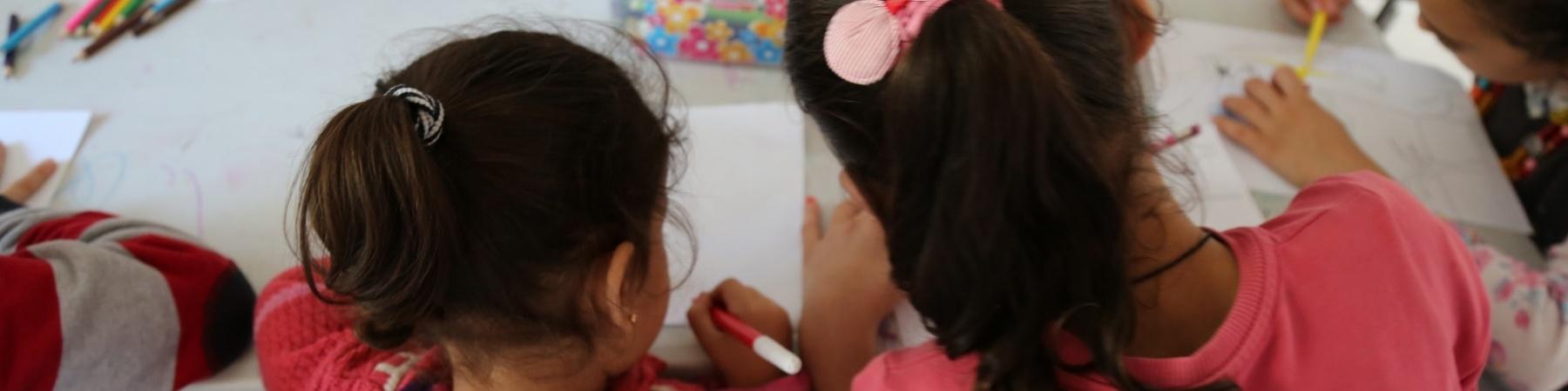 due bambine di spalle al banco di scuola che disegnano