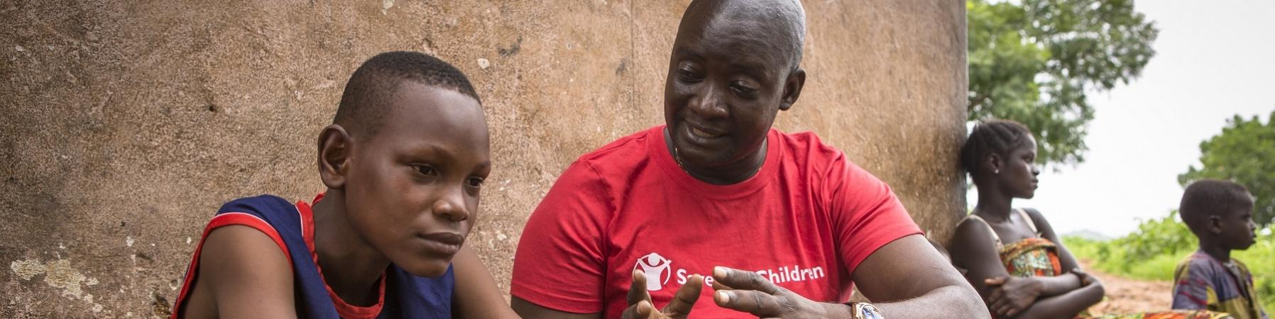 Operatore Save the Children parla con un ragazzo seduto
