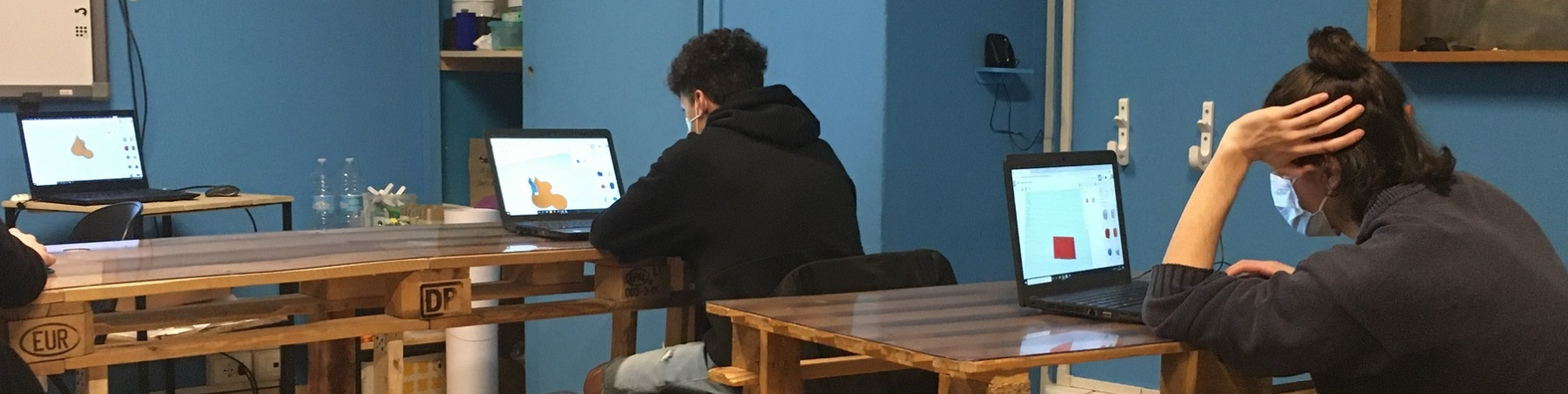 Stanza con tavoli di legno a cui sono seduti due ragazzi adolescenti al computer e ripresi di spalle. Indossano entrambi felpe di colore scuro.