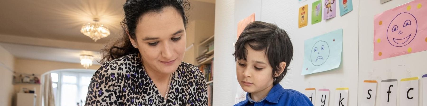 mamma e figlio sfogliano libro con sfondo di una casa e di una libreria con disegni fatti dal bambino