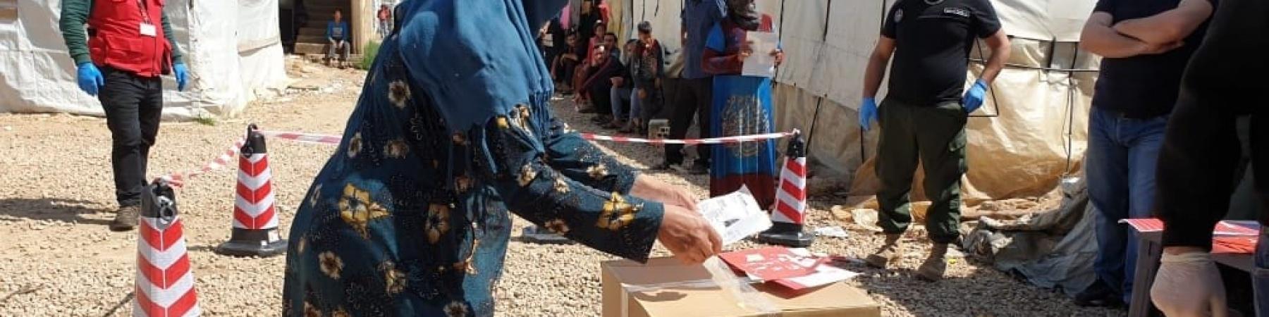 Donna Libanese di profilo mentre prende scatola kit emergenza save the hildren
