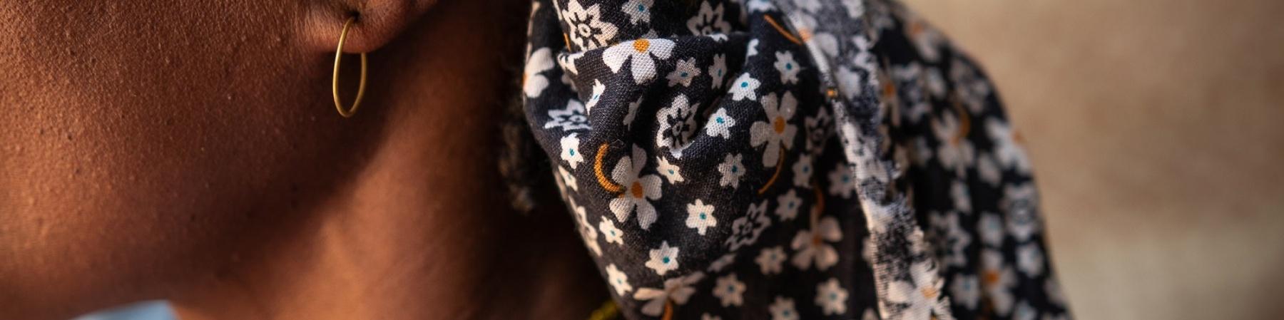 profilo di donna con fascia colorata sul capo, orecchino e collana color ora, indossa una maglietta a righe bianca e nera