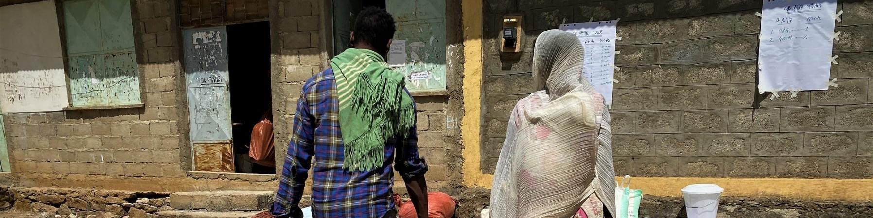 due persone di spalle che camminano verso una casa su un terreno sterrato portando con sè acqua e cibo