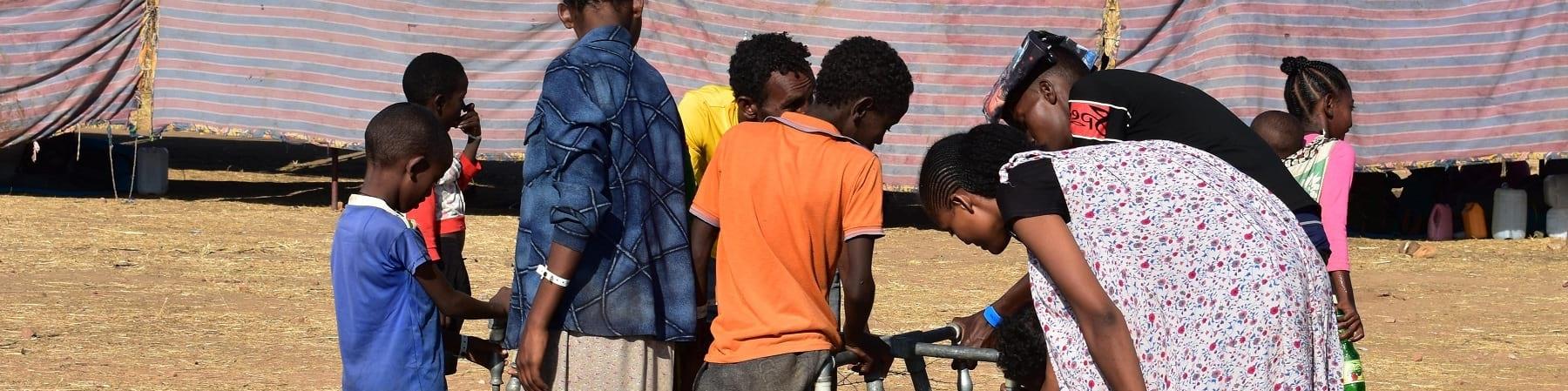 un gruppo di bambini e ragazzi etiopi in un campo per rifugiati si affollano intorno a una fonte d'acqua per raccoglierla con le taniche