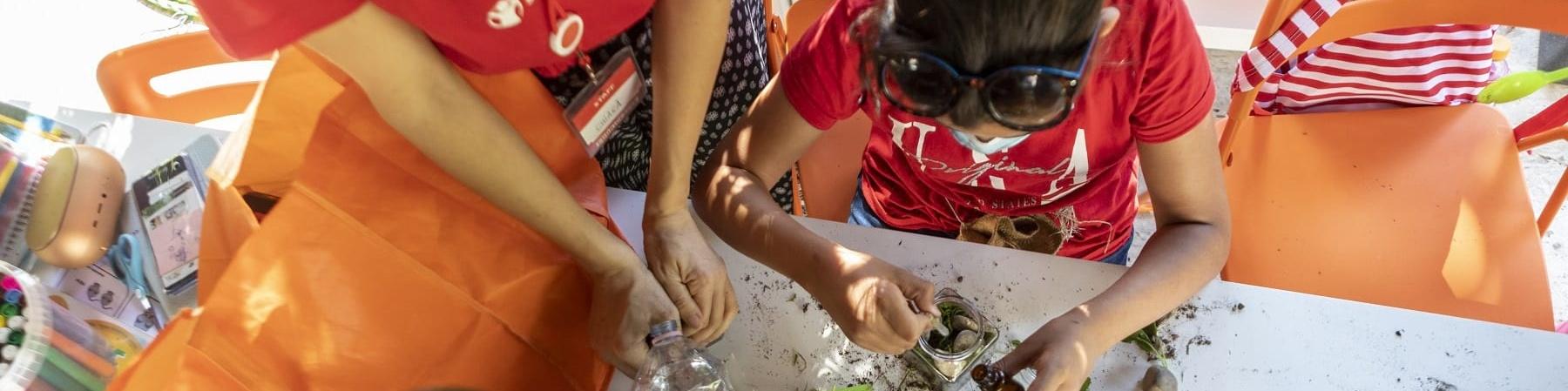 Due bambini giocano con erbe su un tavolo ripresi dall alto