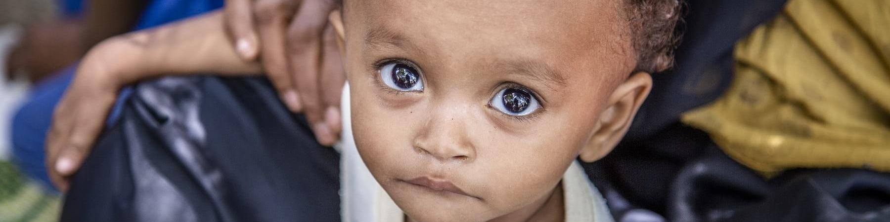 Primo piano di un bambino yemenita tra le gambe di un adulto