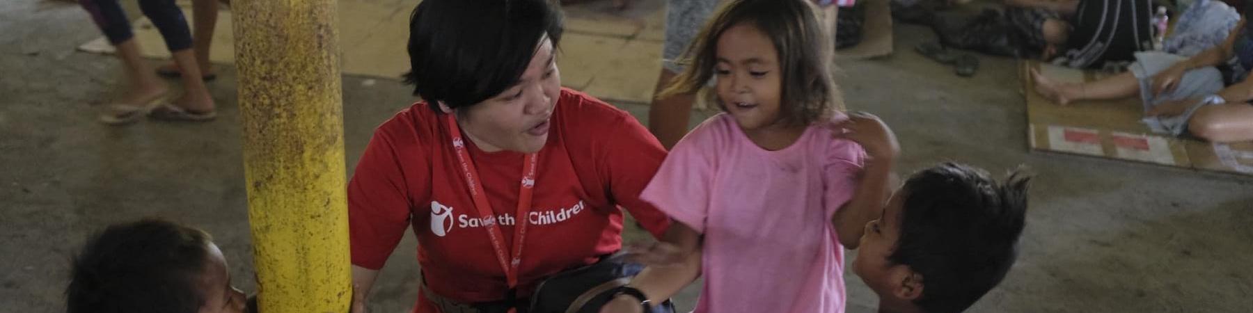 Operatrice save the children parla con bambini in spazio a misura di bambino allestito nelle Filippine per emergenza eruzioni vulcano Taal