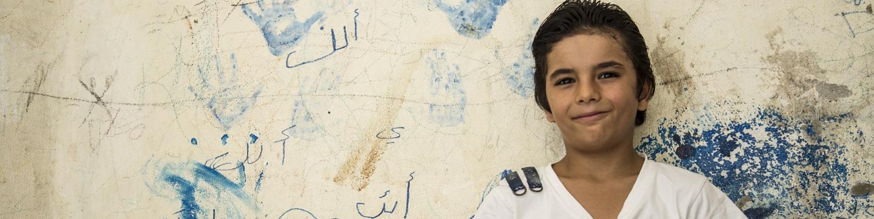 bambino sorridente appoggiato al muro