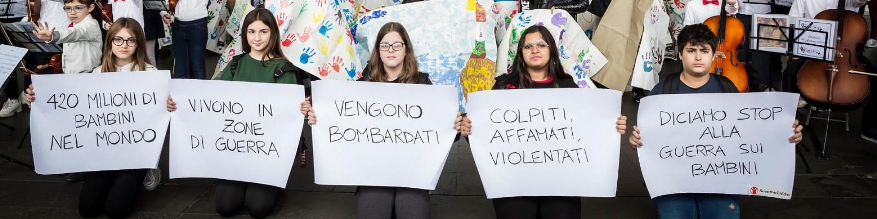Bambini tengono in mano cartelli per flash mob alla Stazione Roma Termini