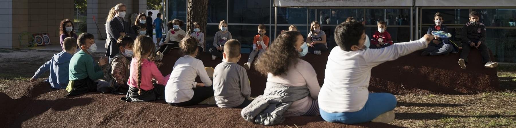 Foto all aperto, una fila di bambini di spalle seduti su un terrapieno guardano due gazebo bianchi montati di fronte a loro