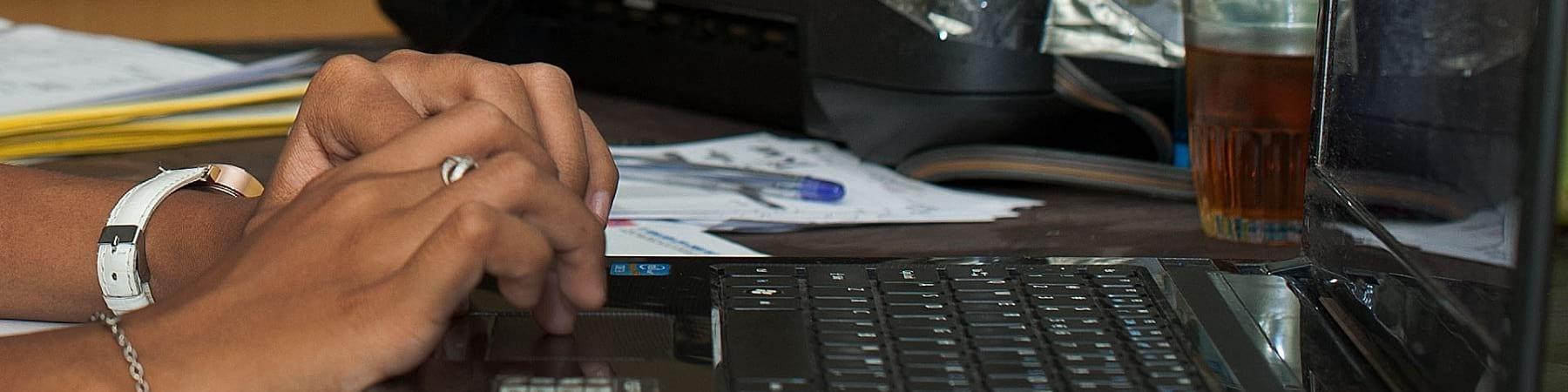 primo piano di mani di ragazza sulla tastiera di un lap top